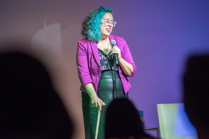 A photo of Leah onstage, a queer woman of colour with blue curly mid length hair, a purple blazer, black shirt, glasses, and a leather skirt. She's using a walking stick and holding a microphone in the other hand.
