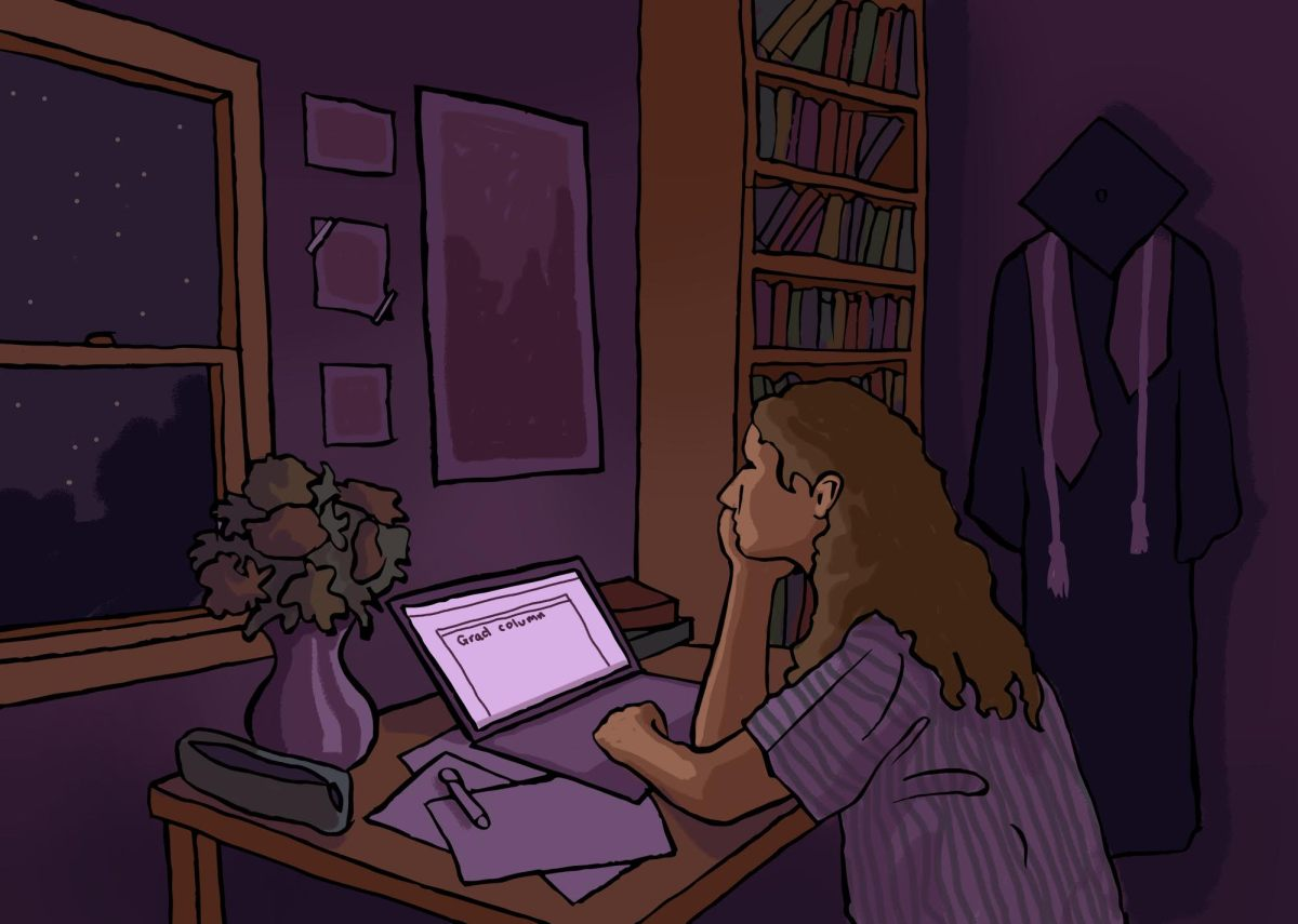 A female student sits at her desk writing her grad column.