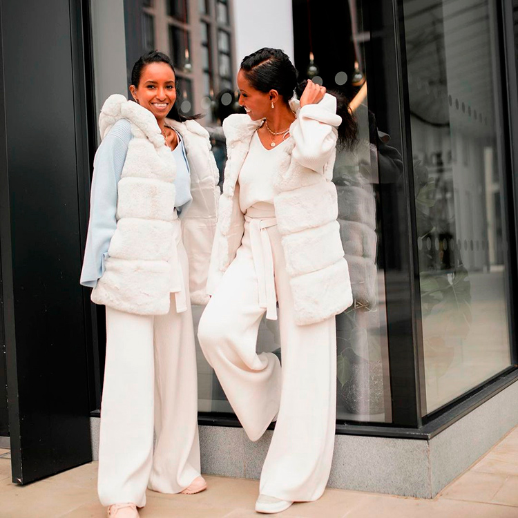 Two sisters with a total River Island white look posing in the streets