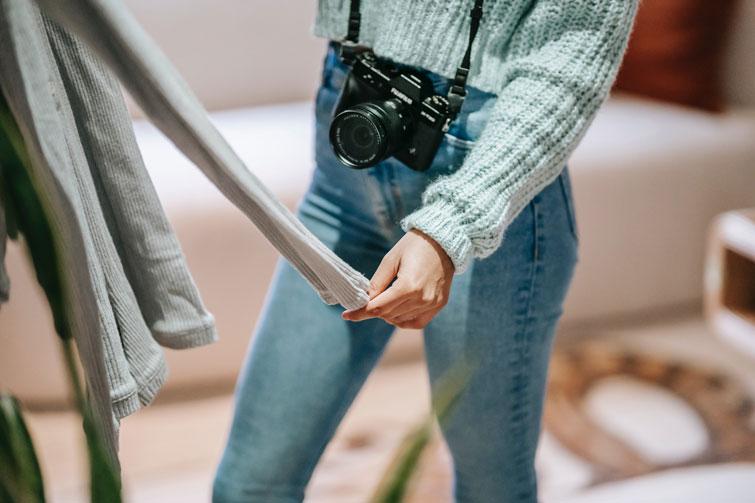 Femme qui va prendre en photo des pantalons et qui va vendre ses vêtements en ligne depuis chez soi