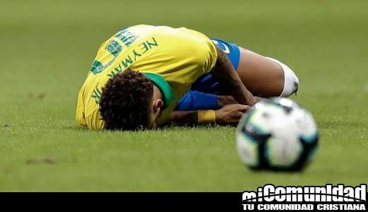 Foto de Neymar tirado en la grama de cancha de futbol deteniendo su rodilla