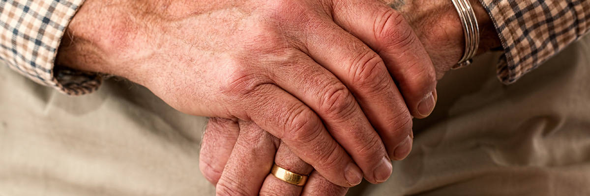 Age and Disability: Closeup of an older gentleman's hands as he rests them on top of a cane.