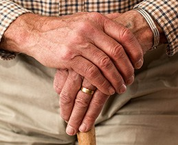 Elderly man's hands overlapping each other on top of cane.