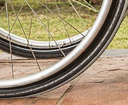 Extreme close up of wheelchair wheels on tile.