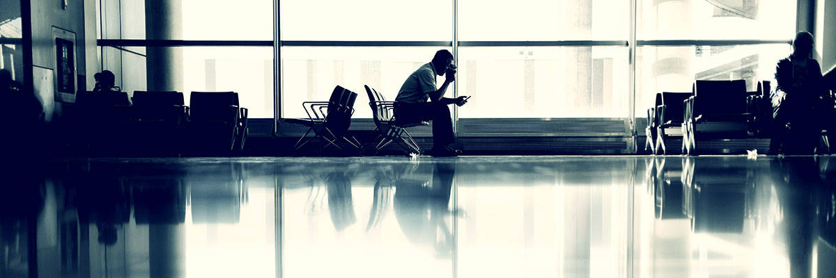 Businessman with phone waiting at the airport. There are different way of tackling distributed workforce training; here are four of them.