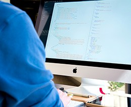 Close up of developer with web code showing on Apple monitor. The US Access Board has formally aligned with WCAG 2.0 and other recognized standards for accessible websites.