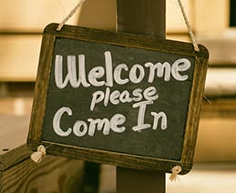 """Chalkboard sign with """"Welcome, Please Come In."""" Advocates remind readers that customer service is one form of disability inclusion."""