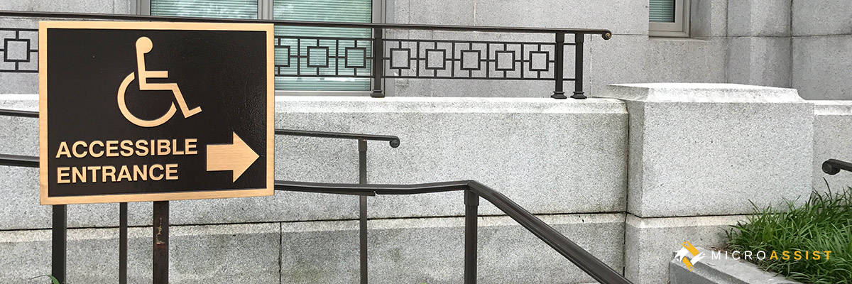 Brass plaque points the way to a government building's accessible entrance. Image copyright 2017, Microassist.