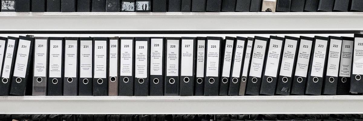 bookshelf of files in labeled binders