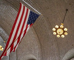 American flag and lights hang from Ellis Island building