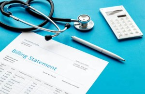 Price Transparency in Healthcare: a billing statement laid out with a pen, calculator, and other medical gear.