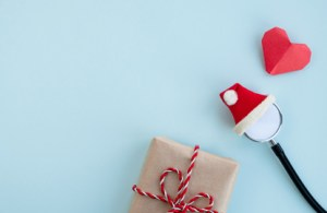 A holiday image with a stethoscope in a Santa hat.