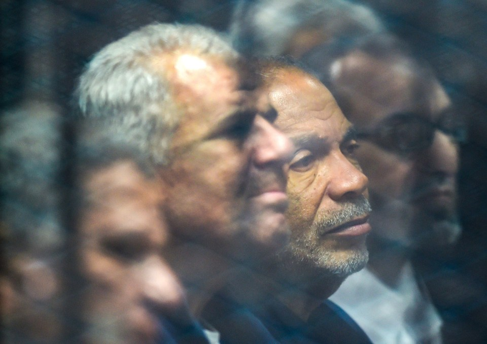Senior Muslim Brotherhood member and former parliament speaker Saad al-Katatni (C-R) sits alongside fellow member Sobhy Saleh (C-L) behind bars in a glass cage during their trial over charges of breaking out of jail during the 2011 uprising against former president Hosni Mubarak's 29-year rule, at a make-shift courthouse in southern Cairo on December 2, 2018.