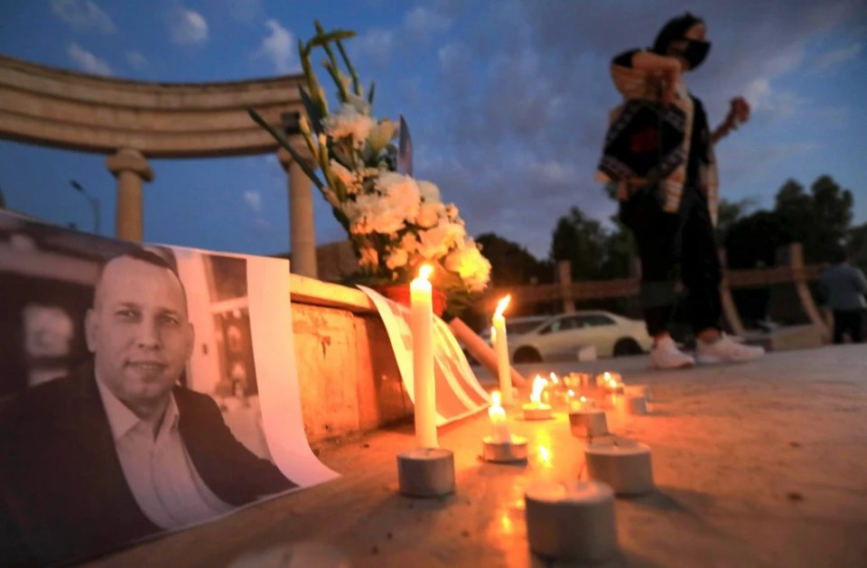 An Iraqi places a candle in front of a poster of slain Iraqi jihadism expert Hisham al-Hashemi, who was shot dead outside his house in the Iraqi capital, during a candlelight vigil in Arbil, the capital of the northern Iraqi Kurdish autonomous region, on July 11, 2020.