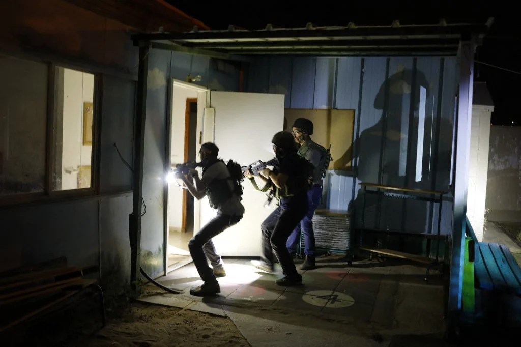 Israeli soldiers and settlers search houses in a West Bank settlement during an all-night army drill in 2018 (AFP)