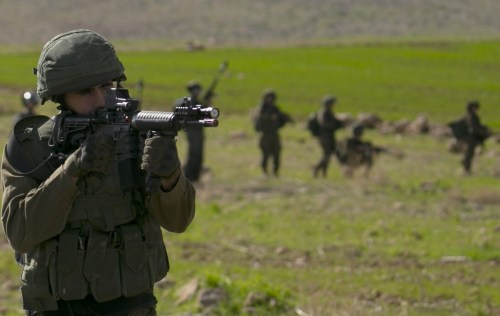 An Israeli soldier aims towards Palestinian protesters near the West Bank village of Tamun on 31 January (AFP)