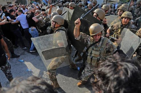 Les forces de sécurité libanaises chargent les manifestants avec des matraques à l'entrée du port de Beyrouth, le 4août2021, au premier anniversaire de l'explosion qui a ravagé la capitale libanaise (AFP)