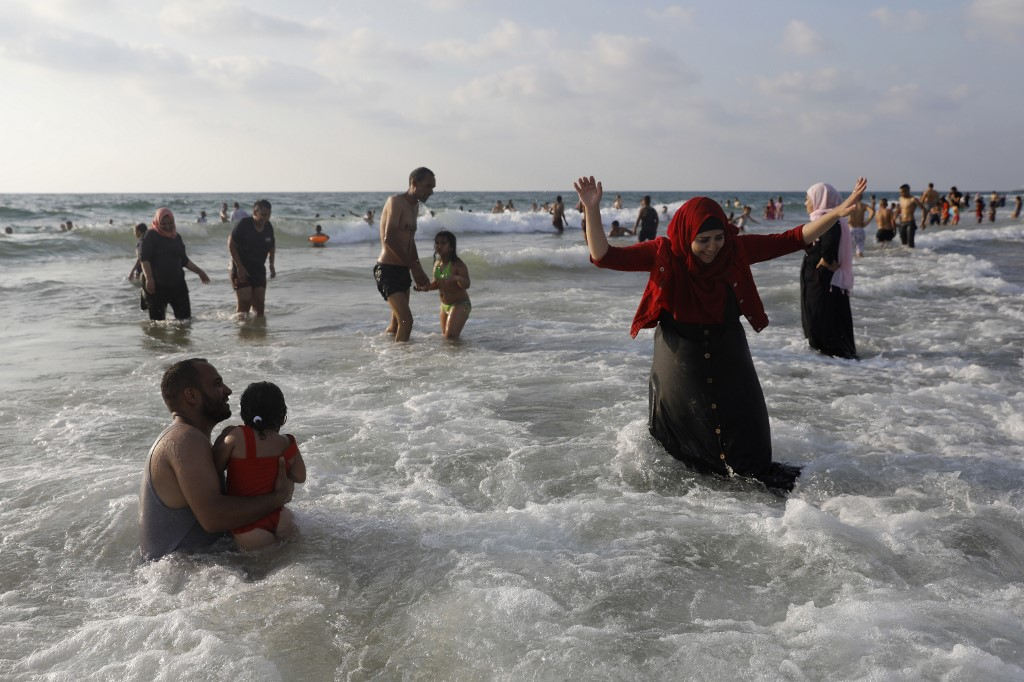Palestinians enjoy the Mediterranean sea on a beach in Tel Aviv during the Eid al-Adha holiday on August 22, 2018. Thousands of Palestinians from the West Bank visited beaches in and around the Israeli commercial capital Tel Aviv during the Eid al-Adha holiday.