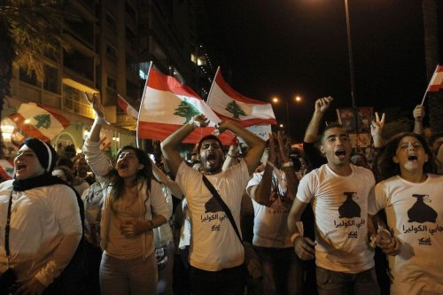 "Lebanese protesters wave the national flag and shout slogans during a demonstration organized by ""You Stink"" campaign, to protest against the country's ongoing trash crisis on 29 October 2015 in the capital Beirut. [ANWAR AMRO/AFP via Getty Images]"