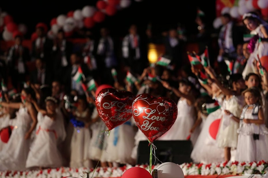 The grooms and their younger sisters doing the traditional Palestinian dance, Dabkeh, to celebrate a mass wedding in Gaza, July 2016 [Middle East Monitor]