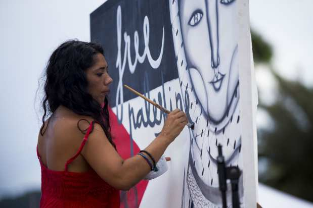 """BARCELONA, SPAIN - SEPTEMBER 14: A woman artist paints a mural in support to the Women Peace Flotilla, two sailing boats named Amal-Hope and Zaytouna-Oliva, with only female activists on board, before it sets off for the Gaza Strip from the port of Barcelona under the banner """"The Women's Boat to Gaza"""" to break the Israeli blockade on Gaza on September 14, 2016 in Barcelona, Spain. ( Albert Llop - Anadolu Agency )"""