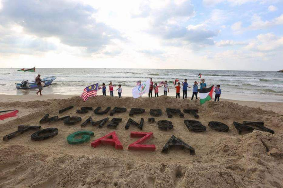 Children stand next to a sand-sculpture in support of the 2016 Women's Boat to Gaza [Flickr / rumboagaza]
