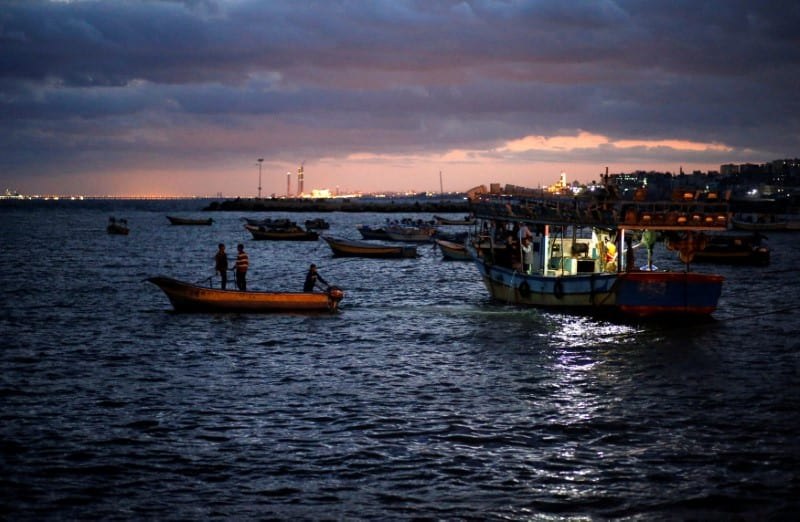 Palestinian fishermen ride their boats as they return from fishing at the seaport of Gaza City on 26 September 2016. [REUTERS/Mohammed Salem]