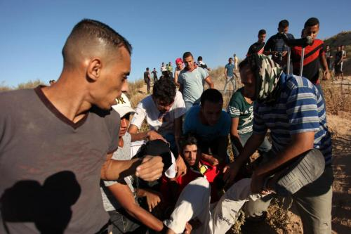 Palestinian protesters carry a wounded comrade during clashes with Israeli security forces near the border between Israel and Central Gaza Strip east of Bureij on 30 Sepember 2016. [APA Images/Ashraf Amra]