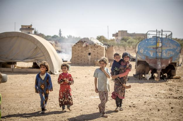 Syrian children play outside their makeshift tents in Turkey [Emin Sansar/Anadolu Agency]