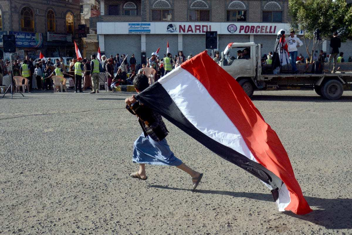 A Yemeni boy holds a national flag during a celebration held for the 53rd Anniversary of Yemen independence from the British occupation at Tahrir square in Sanaa, Yemen on October 15, 2016 [Mohammed Hamoud / Anadolu]