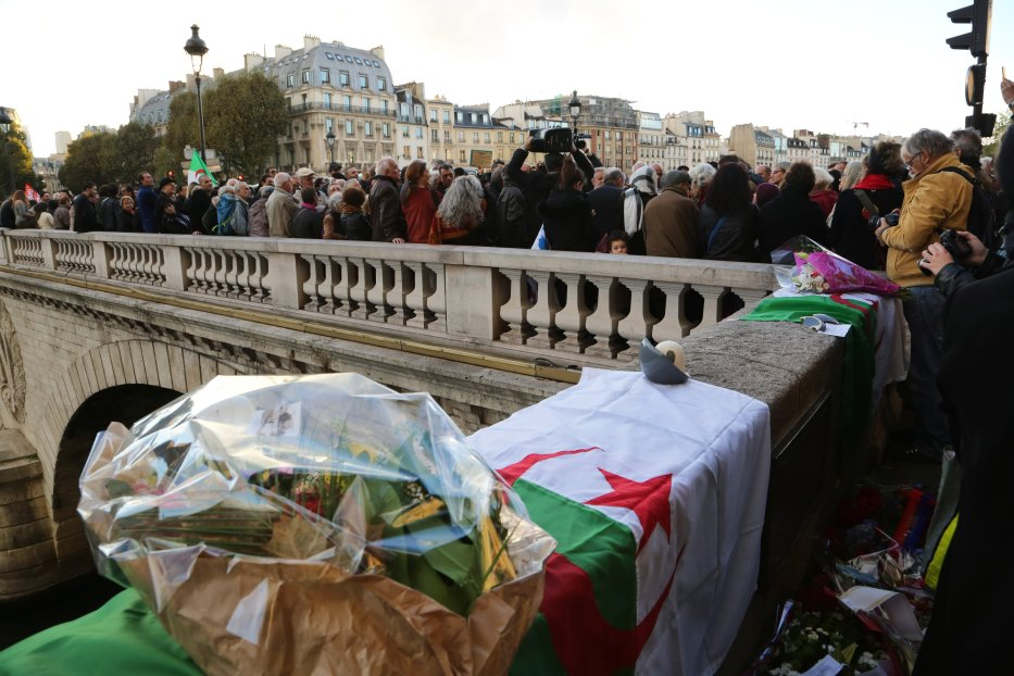People gather during a commemoration ceremony on the Saint-Michel Bridge, near a plaque commemorating the victims of the 17 October 1961 massacre, in Paris, France on October 17, 2016. [Mustafa Sevgi - Anadolu Agency]