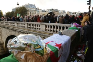 PARIS, FRANCE - OCTOBER 17 : People gather during a commemoration ceremony on the Saint-Michel Bridge, near a plaque commemorating the victims of the 17 October 1961 massacre, in Paris, France on October 17, 2016. ( Mustafa Sevgi - Anadolu Agency )