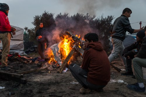 "People warm themselves with a fire in the makeshift camp known as ""the jungle"" near Calais, France on October 24, 2016. [Claire Thomas - Anadolu Agency]"