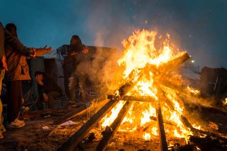 """People warm themselves with a fire in the makeshift camp known as """"the jungle"""" near Calais, France on October 24, 2016. ( Claire Thomas - Anadolu Agency )"""