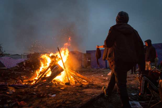Refugees from Afghanistan stand around a fire inside the 'jungle' camp in Calais, France on October 24, 2016. ( Claire Thomas - Anadolu Agency )