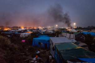 Smoke rises from fires burning inside the 'jungle' camp in Calais, France on October 24, 2016. ( Claire Thomas - Anadolu Agency )