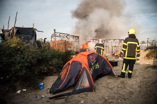 Fire fighters try to extinguish fire at the Calais 'jungle' camp during the third day of evacuation in Calais, France on October 26, 2016 [Anadolu Agency/NnoMan]