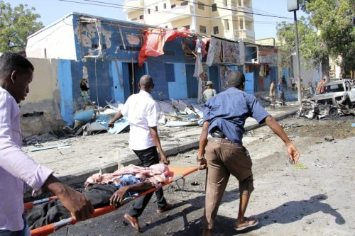 Somali men carry the body of a victim after an explosion at a restaurant, in Mogadishu Somalia, Saturday, Oct. 1, 2016 [AP Photo/Farah Abdi Warsameh]