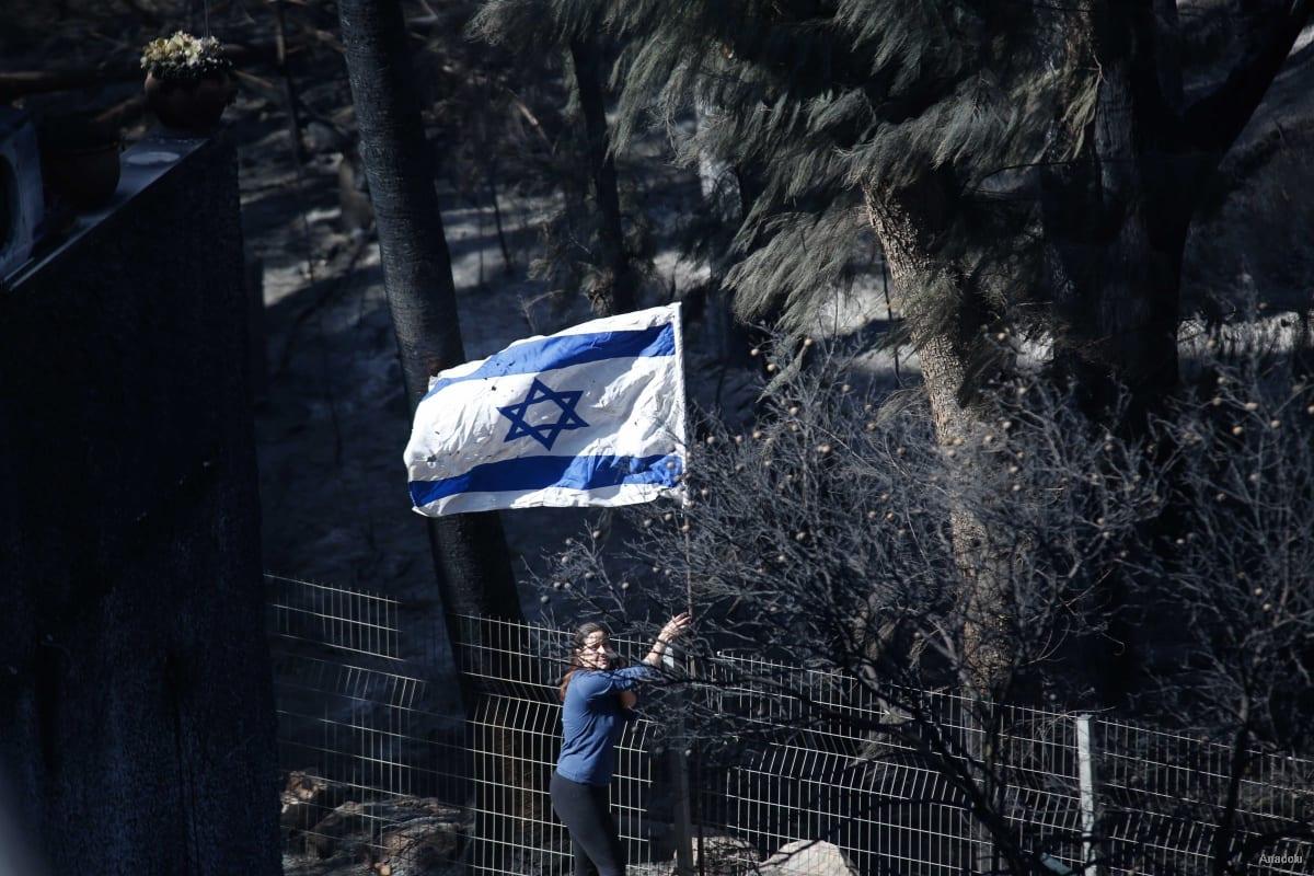 A woman hangs the Israel flag after a forest fire runs through Mount Carmel area in northern Haifa, Israel on November 25, 2016 [Daniel Bar On / Anadolu Agency]
