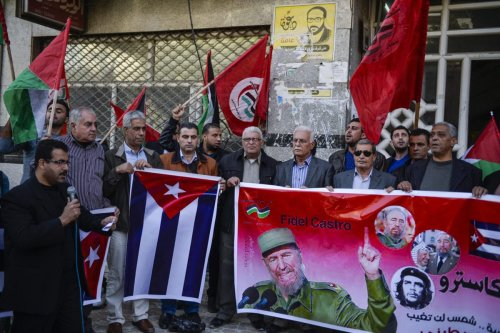 Palestinian People's Party supporters held posters and the National flag of Cuba during a commemoration ceremony of Fidel Castro in front of Shawwa Husary tower in Gaza City, Gaza on November 27, 2016 [Mustafa Hassona /Anadolu Agency]
