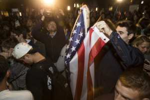 WASHINGTON, USA: A man holds up an American Flag in a crowd of Clinton and Trump supporters that has gather in front of the White House as the results of the 2016 Presidential Election became clear in Washington, USA on 9 November 2016. [Samuel Corum/Anadolu Agency]