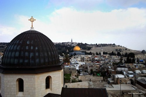 A general view from the tower of the Church of Redeemer shows the Dome of the Rock mosque and the cross of the Church of the Holy Sepulchre in the old city of Jerusalem, on February 17, 2014 [Saeed Qaq/Apaimages]