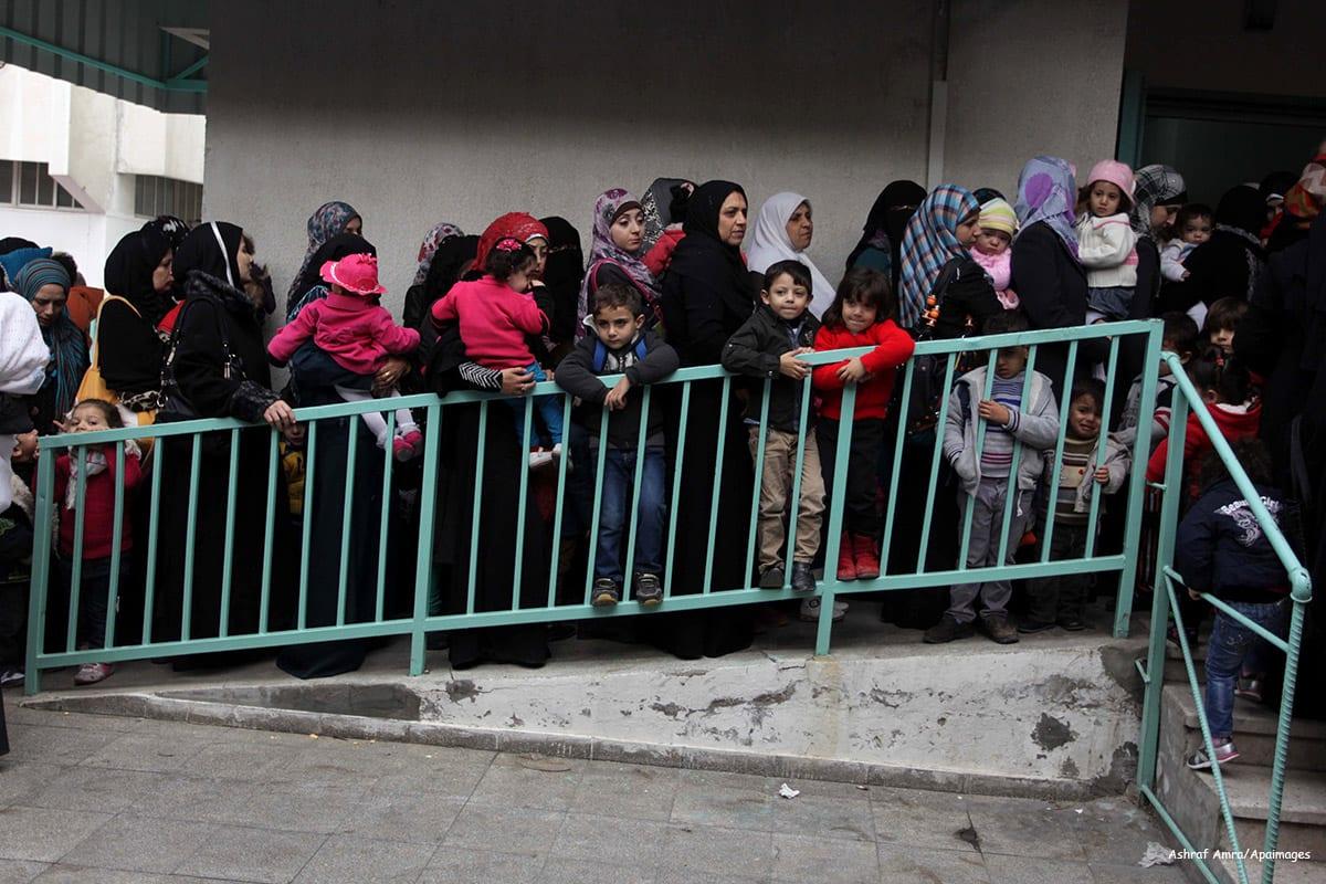 Palestinians wait in line to receive health care in Gaza on December 9 2013 [Ashraf Amra/Apaimages]