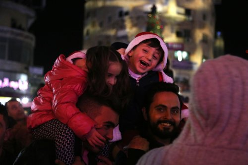 People attend a ceremony to illuminate a Christmas tree planted at the Yasser Arafat square in Ramallah, West Bank on December 4 2016 [Issam Rimawi/Anadolu Agency]