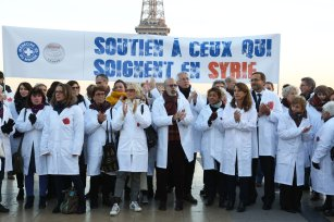 Members of the World Doctors association stage a protest, condemning massacres and attacks in Syria's Aleppo over civilians within the on going civil war at the Trocadero square close to the Eiffel Tower in Paris, on December 8, 2016. ( Mustafa Sevgi - Anadolu Agency )