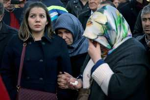 Women cry as people leave carnations for the victims of Istanbul terror attacks near the Vodafone Arena in Istanbul's Besiktas, Turkey on December 11, 2016 [Onur Çoban / Anadolu Agency]