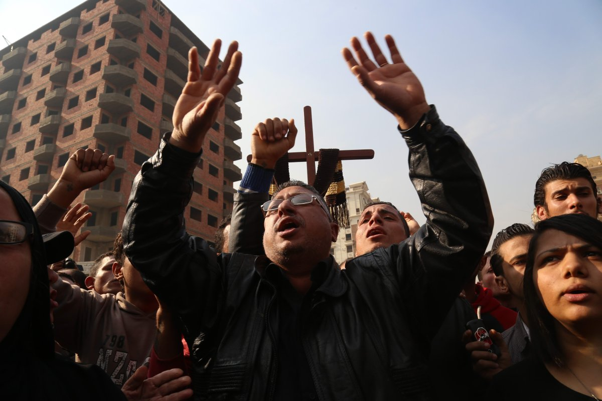 People react during the funeral ceremony for the victims of the explosion at Saint Peter and Saint Paul Coptic Orthodox Church in Abbasiya district, at Church of the Virgin Mary in Nasr City neighbourhood of Cairo, Egypt on 12 December, 2016 [Ahmed Gamil/Anadolu Agency]