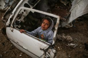KHAN YUNIS, GAZA - DECEMBER 14: A Palestinian child is seen near a car wreck as Palestinians living in makeshift homes in El-Zohor neighborhood in the city of Khan Yunis on the Gaza Strip are facing difficult conditions under the cold weather on December 14, 2016. The economy and their living conditions are getting progressively worse due to Israel's embargo on Gaza. ( Mustafa Hassona - Anadolu Agency )