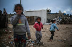 Palestinian children play outside makeshift homes in Gaza [Mustafa Hasson/Anadolu Agency]