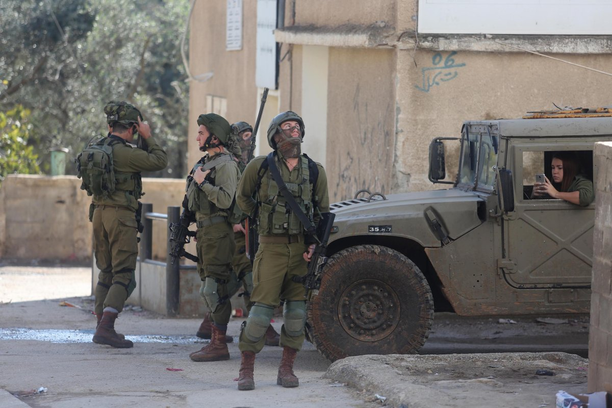 Israeli soldiers are seen as they storm Palestinians' houses and shops during an operation carried out after opening fire at a Jewish at Shuqba villiage in Ramallah, West Bank on December 19, 2016 [Issam Rimawi / Anadolu Agency]